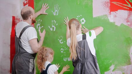 The family in overalls with rollers are painting a white wall with green paint - indoor