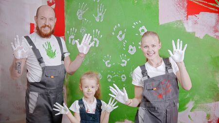 Happy successful family are putting their white handprints on a green wall - looking in the camera