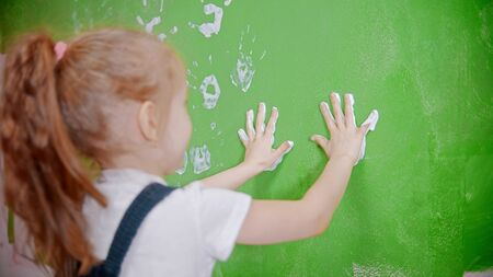 A little girl stamping her handprints on the wall