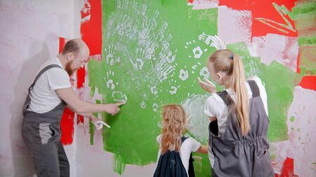 Happy family are putting their white handprints on a green wall - dad drawing something on the wall. Mid shot
