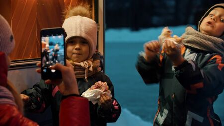 A woman mother taking photos of her children outdoors in winter