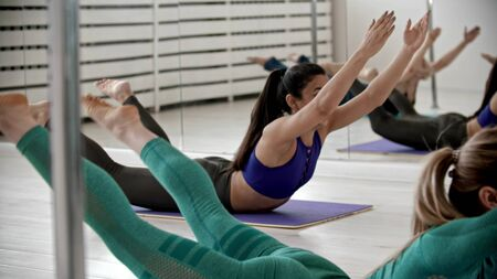 Young women training lying on the yoga mat - lying on the stomach and performing exercises