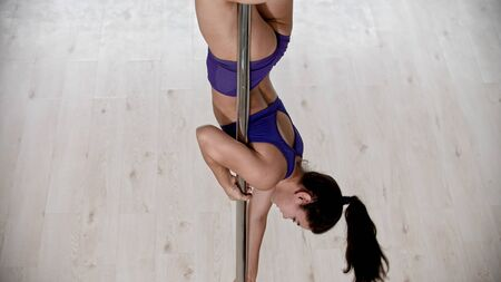 A strong woman with long hair hanging on the pole upside down Reklamní fotografie