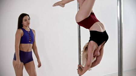 A blonde woman having a pole dancing training in the studio - keeping the balance upside down - her trainer watching her