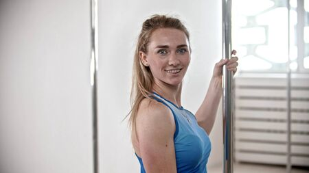 Smiling attractive woman standing by the pole in the bright fitness studio