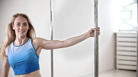 Smiling attractive woman holding a pole in the bright fitness studio Reklamní fotografie