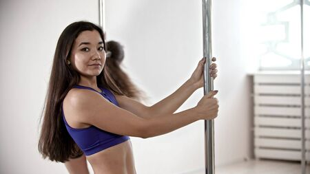 Two sportive women having a pole dancing training in the white studio - one of them looking in the camera and smiling
