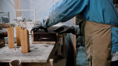Concrete industry - worker preparing glass and silicone for the working on the souvenir statue - putting it in wooden separation compartment