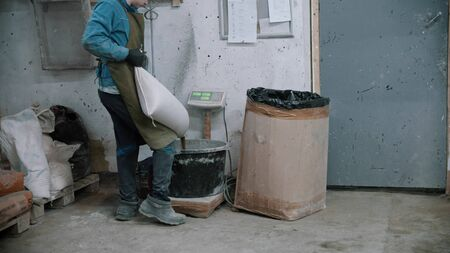 Concrete industry - man worker puts dry cement in a bucket. Mid shot Imagens