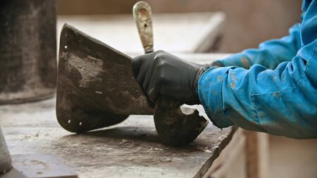 Concrete industry - man worker cleaning the form for concrete casting out from the leftovers. Mid shot Imagens