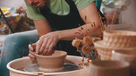 Pottery - a man with an iron spatula is helping himself maintaining the shape of a bowl - indoor