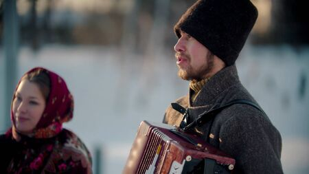 Russian folklore - russian bearded man playing accordion outdoors and woman standing next by him