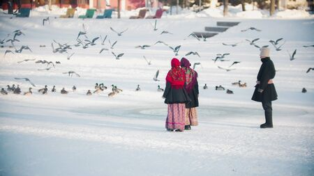 Russian traditions - people in beautiful clothes are chasing pigeons on a frozen pond - outdoor Stok Fotoğraf