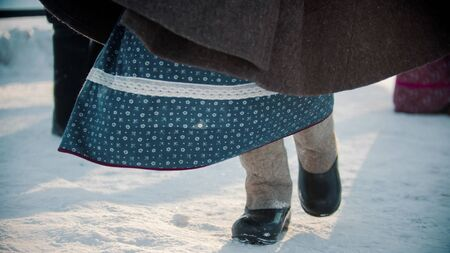 Russian traditions - a girl in felt boots and a dress dancing at winter - outdoor