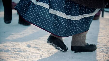 Russian traditions - a woman in felt boots and a dress dancing at winter - outdoor