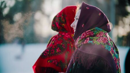 Russian folklore - a woman in a bright shawl standing outdoors in the winter forest - outdoor