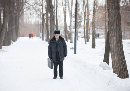 An old man with suitcase standing outdoors in winter park while snowfall Stock Photo