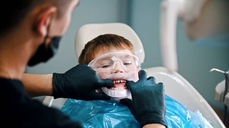 A little boy with baby teeth having a cleaning treatment in the clinic - the dentist puts a mouth-opener in the mouth 免版税图像