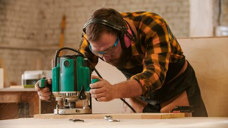 Carpentry industry - man cutting out the patterns out of the wooden plank Reklamní fotografie
