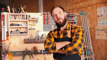 Bearded man worker in yellow shirt standing in the workshop - crossing his hands Foto de archivo