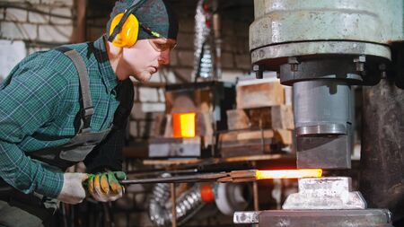 Blacksmith - putting a longer piece of metal under the pressure of industrial forging machine Standard-Bild