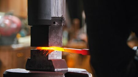 Forging an object out of hot metal using an industrial pressure machine