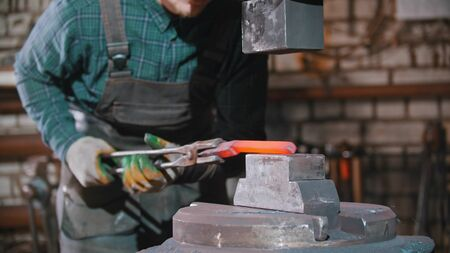 Forging an item out of hot longer piece of metal using a pressure machine Standard-Bild