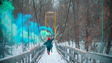 Two young women running on the bridge having fun with green and blue smoke bombs - mid shot Stockfoto