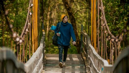 Young free man traveler with big backpack walking on the bridge in the forest Imagens
