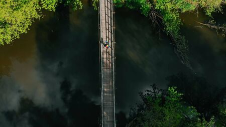 Young person walking on the rope bridge in the forest Imagens