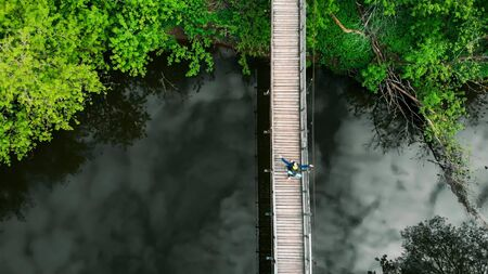 Young happy man traveler with big backpack walking on the bridge in the forest. Mid shot