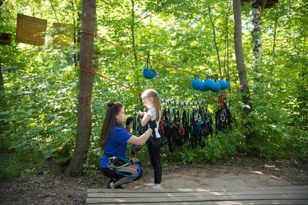 Rope adventure - a woman instructor puts on the insurance pendants on the waist of a little girl Reklamní fotografie