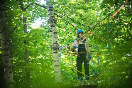 Rope adventure in the forest - woman standing on the stand attached to the tree and looking straight