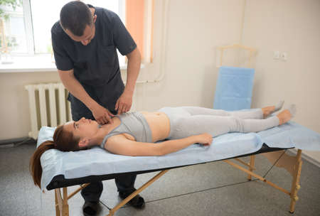 Young woman having osteopathic treatment in the clinic with professional doctor. Mid shot