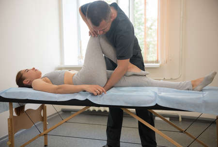 Young woman having osteopathy treatment - the doctor bending her leg in the knee. Mid shot