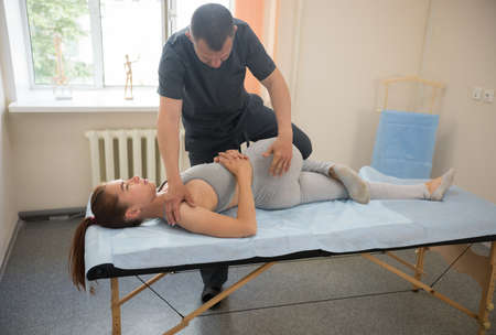 Young woman having osteopathy treatment - the doctor bending her lower part of the body. Mid shot Standard-Bild