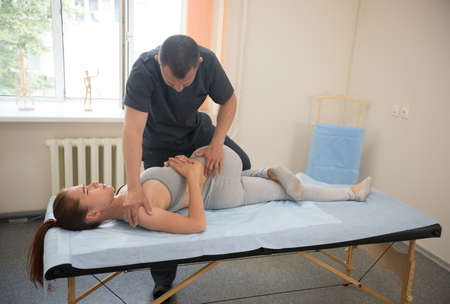 Young woman having osteopathy treatment in the clinic - the doctor bending her lower part of the body. Mid shot