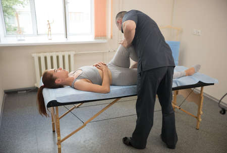 Young woman having osteopathy treatment - the doctor bending her legs while she lying on the couch. Mid shot
