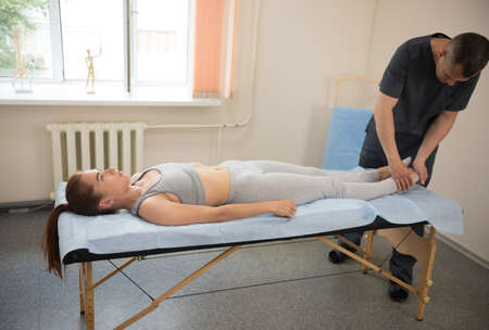 Young woman having osteopathy treatment in the clinic - massaging the foot. Mid shot