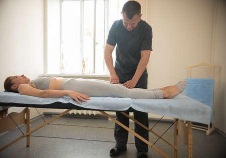Young woman having osteopathy treatment - the doctor massaging her leg. Mid shot Standard-Bild