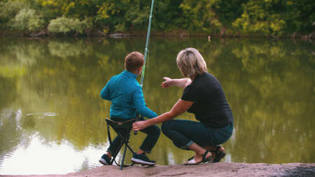A little boy with his mother on fishing on nature. Mid shot
