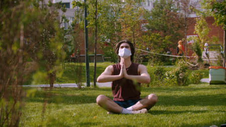 A young man in the medical mask sitting on the grass and meditating Standard-Bild