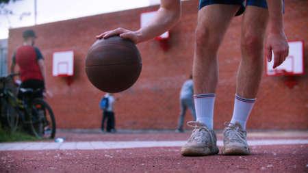 Young man on basketball playground hitting the ball