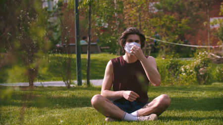 A young man sitting on the grass in medical mask