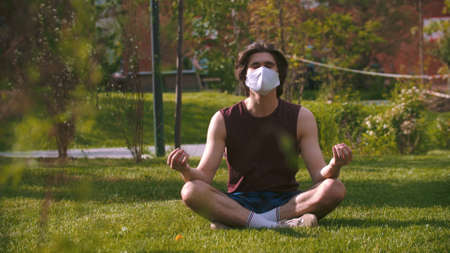 A young man in the medical mask sitting on the grass in the park and meditating Standard-Bild