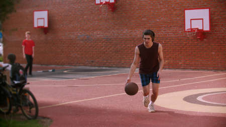 Young man running on the basketball playground and hitting the ball Standard-Bild