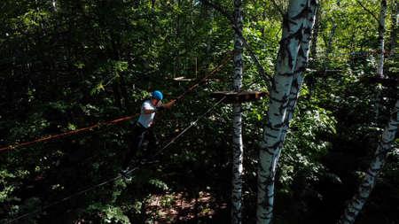 Rope adventure - man walking on the rope between trees