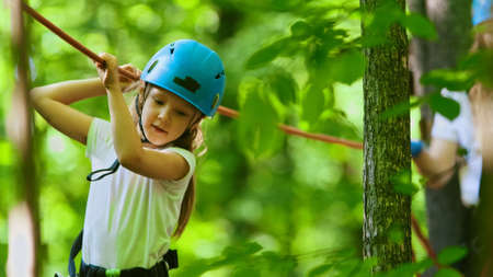 A little girl having a rope adventure in the forest