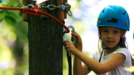 Rope adventure - a girl with an insurance hook attached to the rope