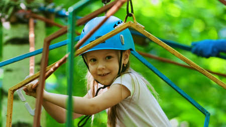 Rope adventure - smiling girl with an insurance hook attached to the rope crossing the rope bridge
